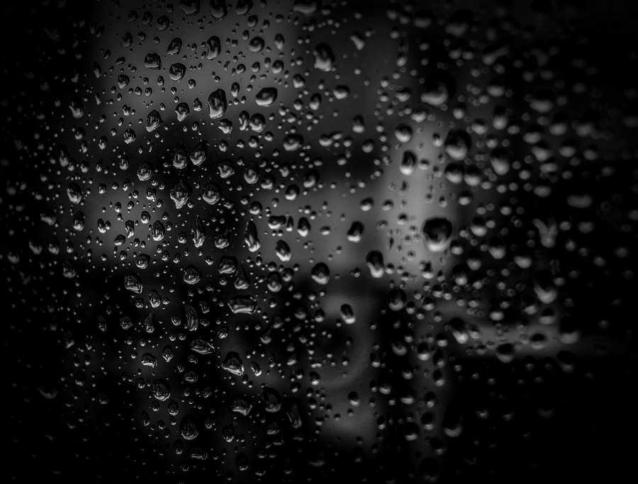 Close up of water drops on a reflective black surface.