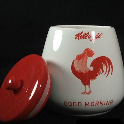 "A white ceramic cookie jar with a red lid. The jar is decorated with a drawing of a rooster and the words: ""Kellogg's, Good Morning"""