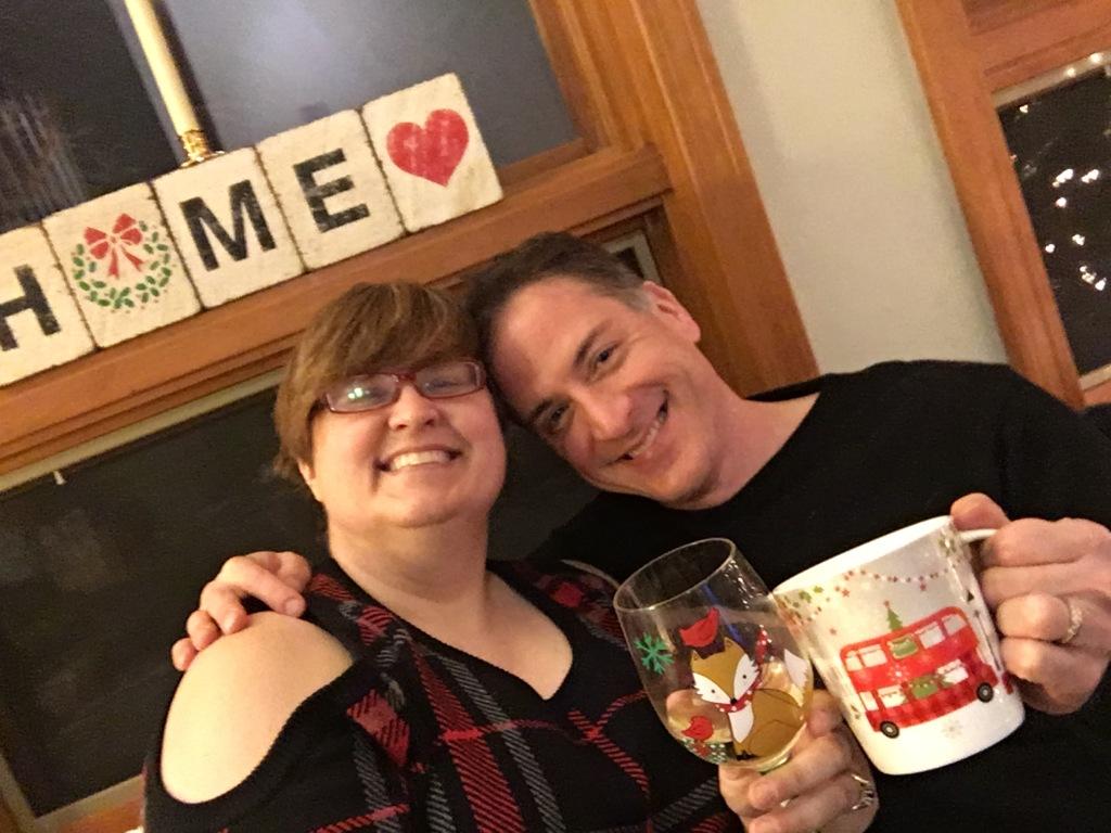 Picture of MezzoSherri and Mr. Mezzo, toasting the camera with a glass of wine (Sherri) and a mug of coca (Mr. Mezz)