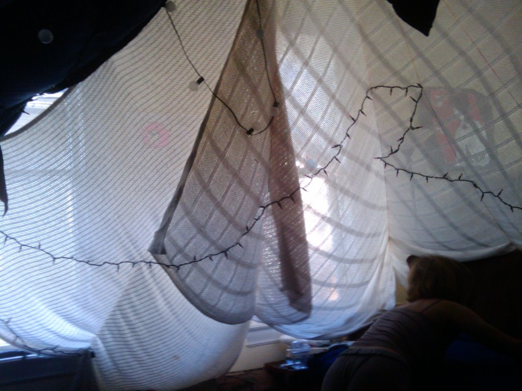 Photo taken from the inside of a blanket fort. Sunlit windows can be seen through the white blankets suspended above the camera's position, which are also adorned with stings of decorative lights.