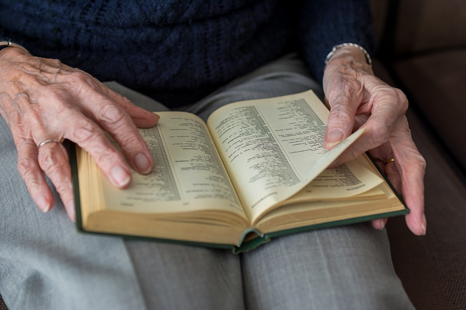 Close up image of an old woman's hands turning the pages of a book.