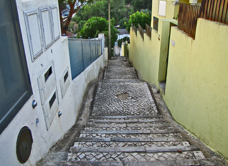 Looking down a long concrete and cobblestone staircase between two rows of houses.