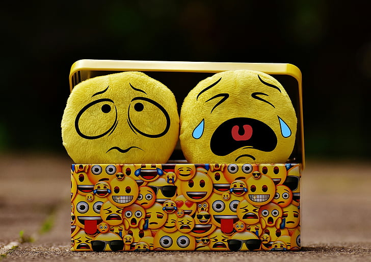 A picture of two plush emojis--one scared, one crying--in a box decorated with a wider variety of emoji faces.