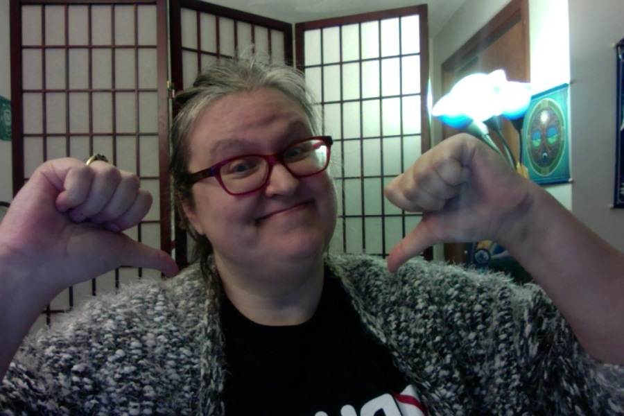 Picture of Sherri, a Caucasian human, with a snarky smile pointing to herself with both thumbs.