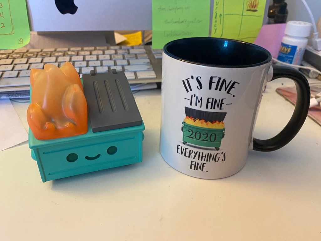 "Close-up of 2 objects: on the left, a Funko Pop dumpster fire; on the right, a coffee mug with a photo of a dumpster labeld ""2020"" on fire, with the surrounding text: It's ine, I'm fine, everything's fine."""