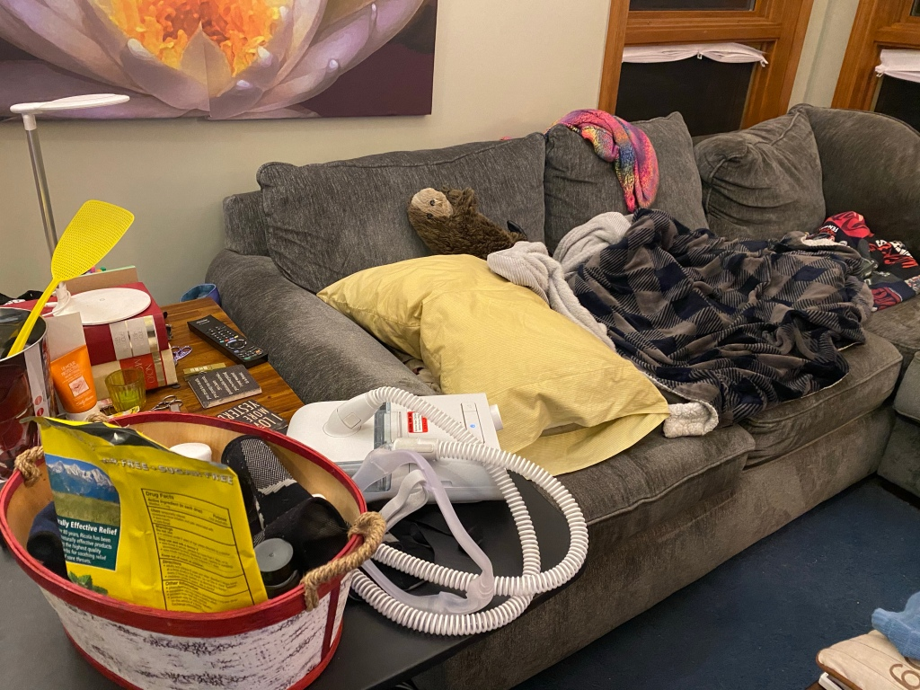 "A ""sleeping nest"" of blankets on a grey couch, with a TV table in the foreground holding a CPAP machine and a basket of bedside essentials (cough drops, meds, eyeshade, etc.)"