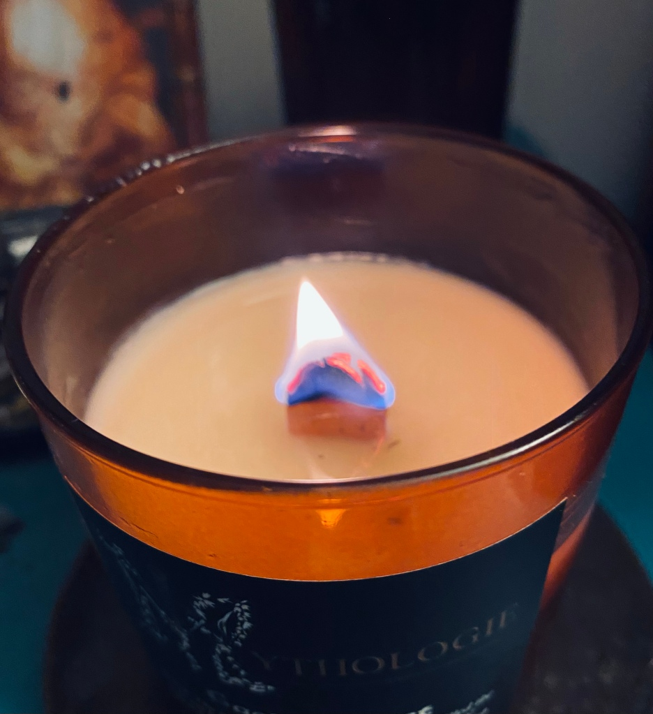 A close-up of a burning wooden wick in a candle in an amber-colored jar.