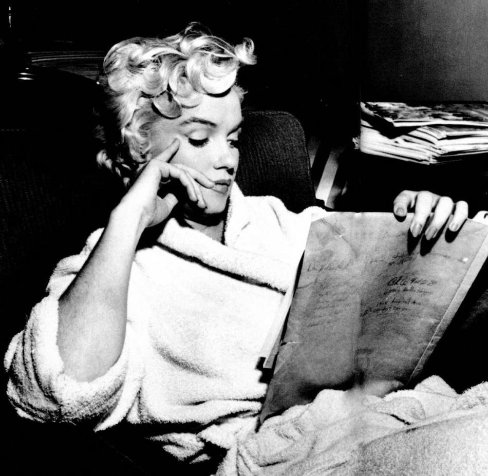 A black and white photo of Marilyn Monroe, in a white terrycloth bathrobe. She has a pensive look on her face as she reads, looking at the book in her hand rather than at the camera.