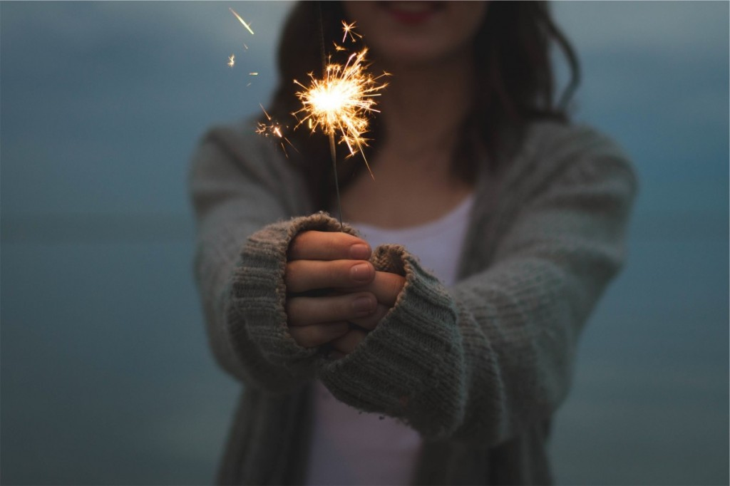Closeup of a young woman's hands holding a lit sparkler.