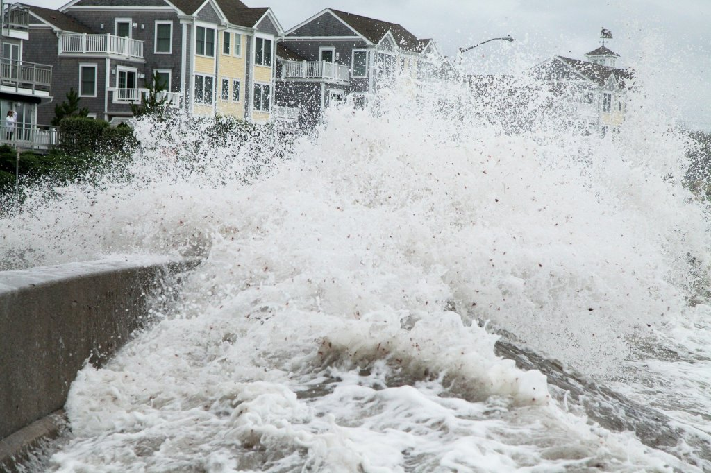 Photo of a storm surge going over a concrete embankment and threatening a row of beach houses.