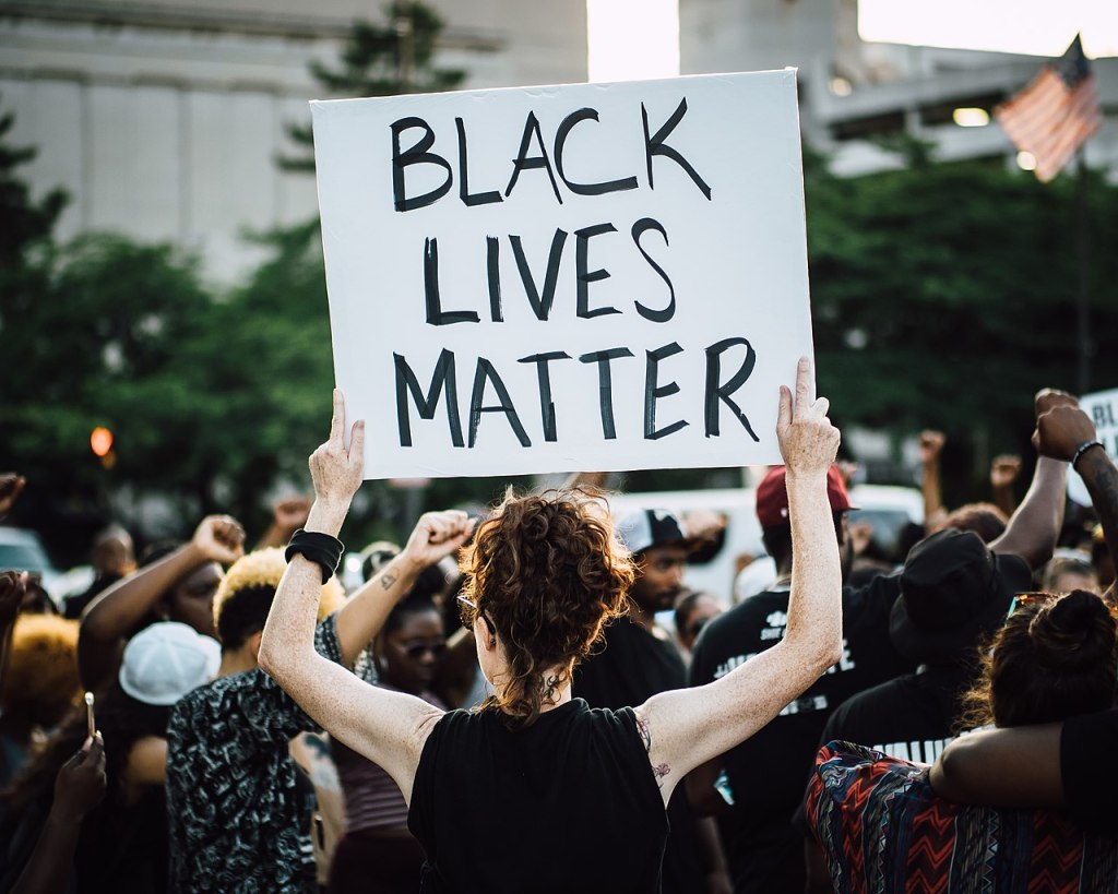 "A Black Lives Matter march attended by men and women, primarily POC. In the center of the frame, a fair-skinned female-presenting human is seen from behind. She holds a sign reading ""Black Lives Matter"" above her head."