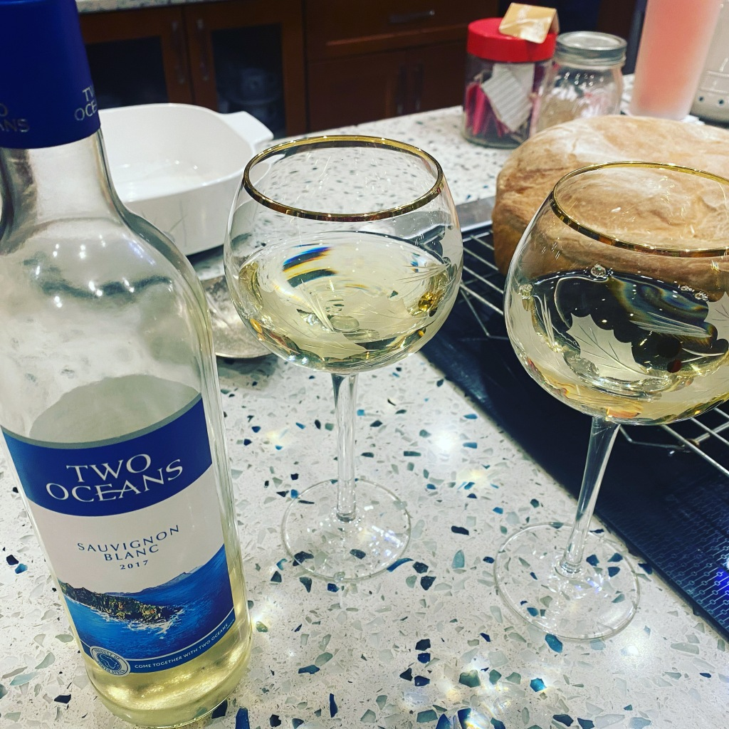 A bottle of white wine next to two filled wine glasses. In the background, a fresh-baked loaf of bread sits on a cooling rack.