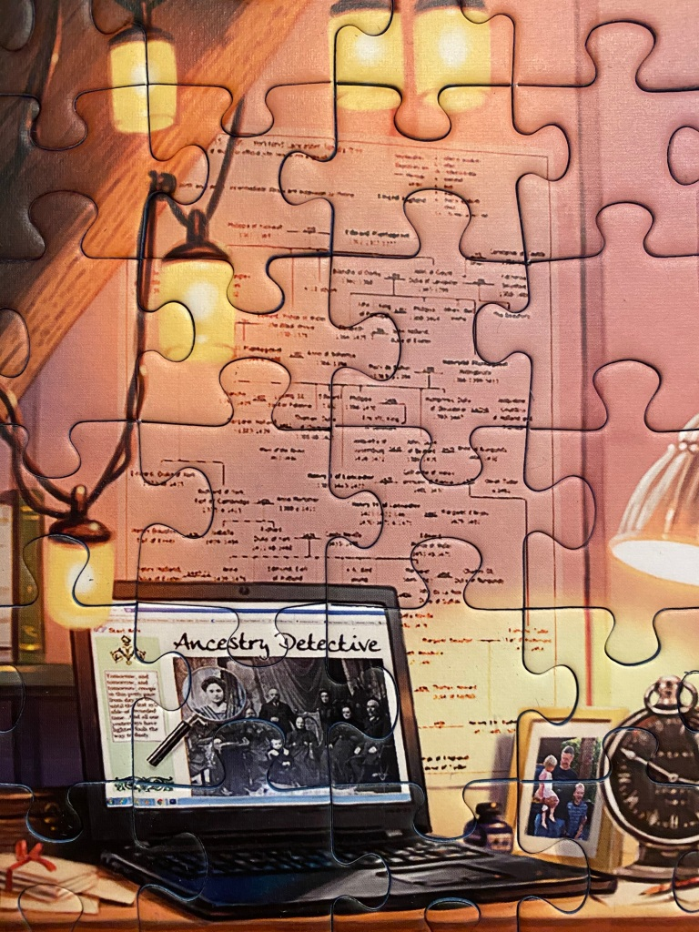 "Close-up of a completed jigsaw puzzle, showing an open laptop at the (fictional) site ""Ancestry Detective."" There is also a poster with a hand-written family tree on the wall above the desk & laptop."