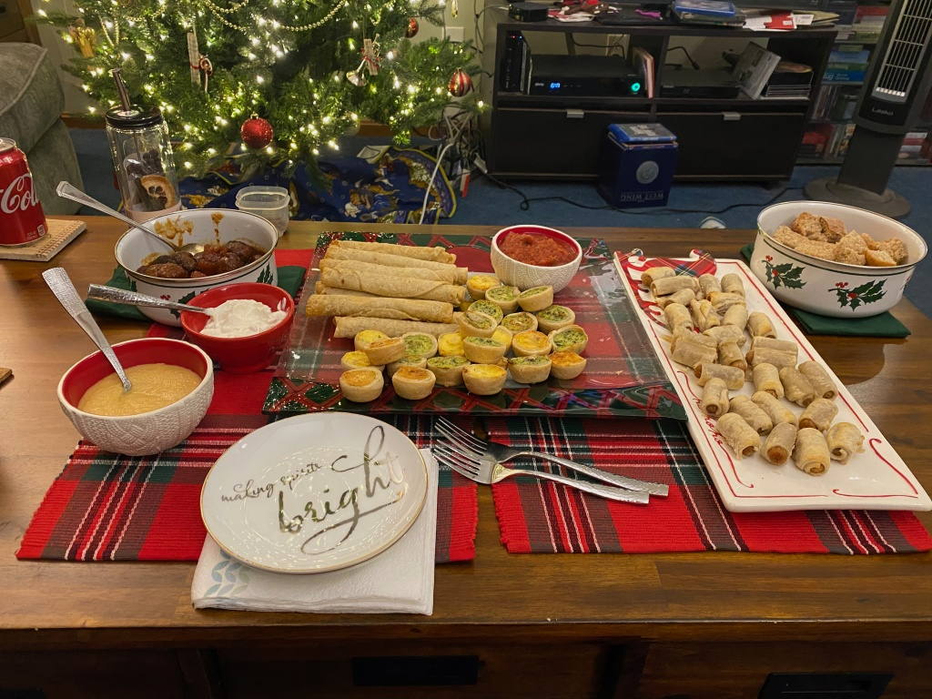 """A spread of appetizers---mini quiches, pigs-in-blankets, taquitos, maple-glazed meatballs---on a coffee table. In the foreground is a plate reading """"making spirits bright"""""""