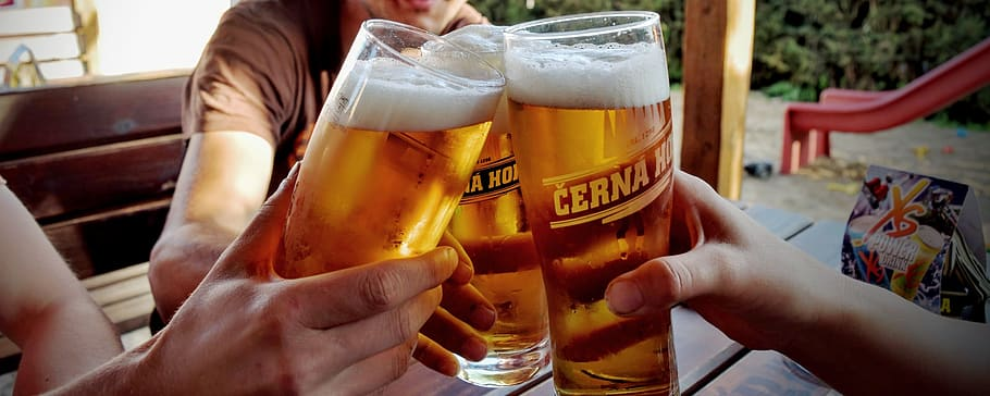 Three beer glasses being clinked together in a toast.