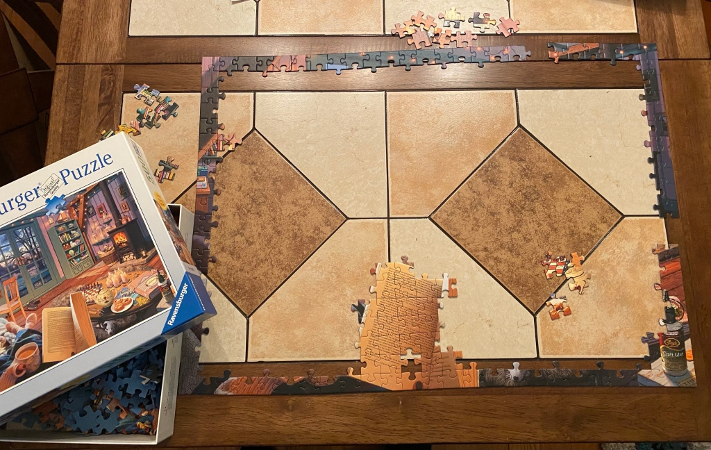 Picture of a jigsaw puzzle being assembled. The edge is mostly done, and the box of puzzle pieces is to the left of the puzzle-in-progress.