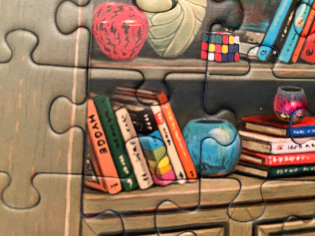"Close-up of a completed jigsaw puzzle, showing bookshelves holding vases, a rubik's cube and several books--the one book with a readable title says ""Hygge"""