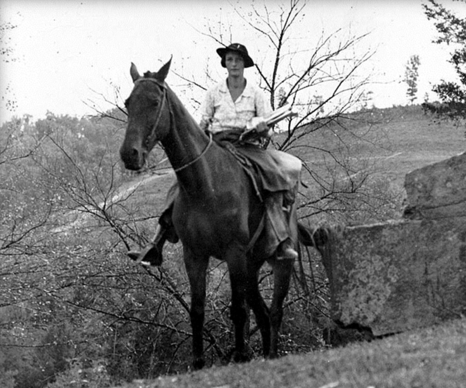 A black and white photo of a packhorse librarian, astride her horse with an armful of reading materials.