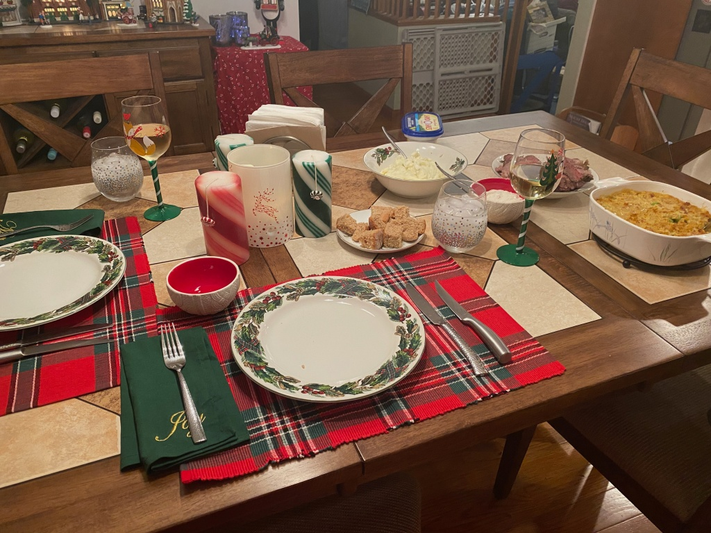 Dinner table set for Christmas dinner, with various serving dishes containing mashed potatoes, sliced roast, sour cream horseradish sauce, and broccoli corn casserole.