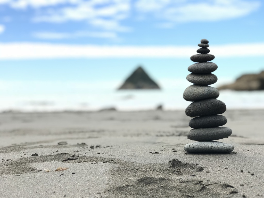 A closeup of a small stone cairn sitting on an empty beach. The water line and sky are out-of-focus behind the cairn.