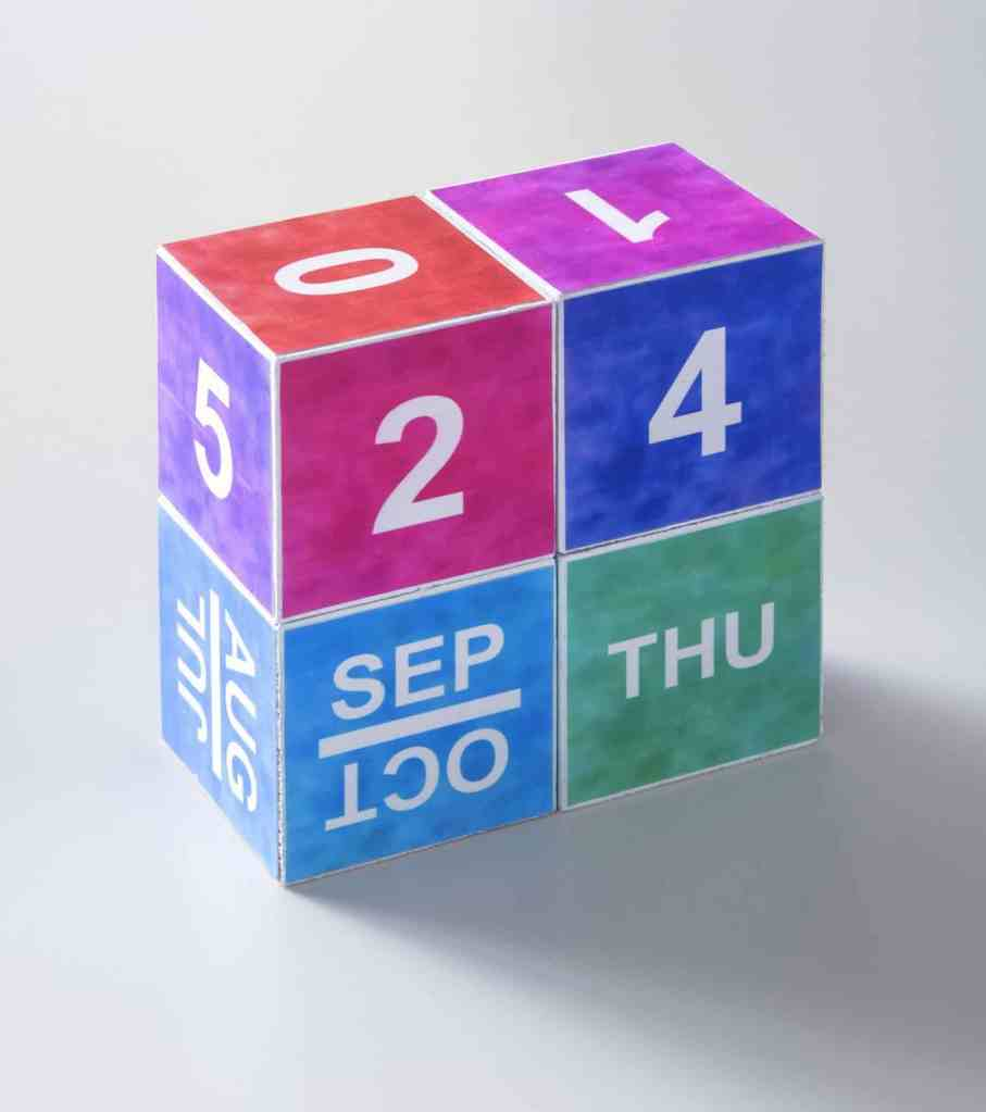 A perpetual block calendar, with multicolored blocks showing the date Thursday, September 24. The blocks are photographed at an angle so you can see some of the other months and numbers on the un-used sides of the blocks.
