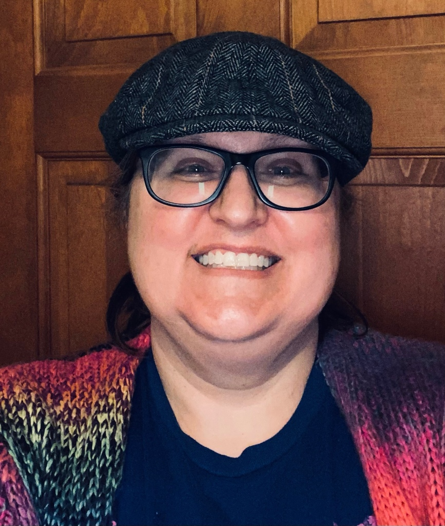A selfie of me, a white female, smiling into the camera, wearing a wool newsboy cap and glasses with dark frames.