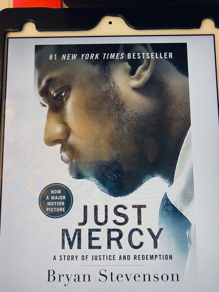 An iPad displaying the movie tie-in edition of the eBook for Just Mercy. Superimposed over a photo of Michael B. Jordan (the actor who plays Stevenson) is the following text: #1 New York Times Bestseller Now a Major Motion Picture Just Mercy: A Story of Justice and Redemption Bryan Stevenson