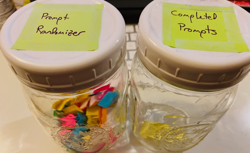 """Two mason jars sitting side by side. The one on the left is labelled """"Prompt Randomizer"""" and contains many small bits of folded paper. The one on the right is labelled """"Completed Prompts"""" and has one slip of paper in it."""