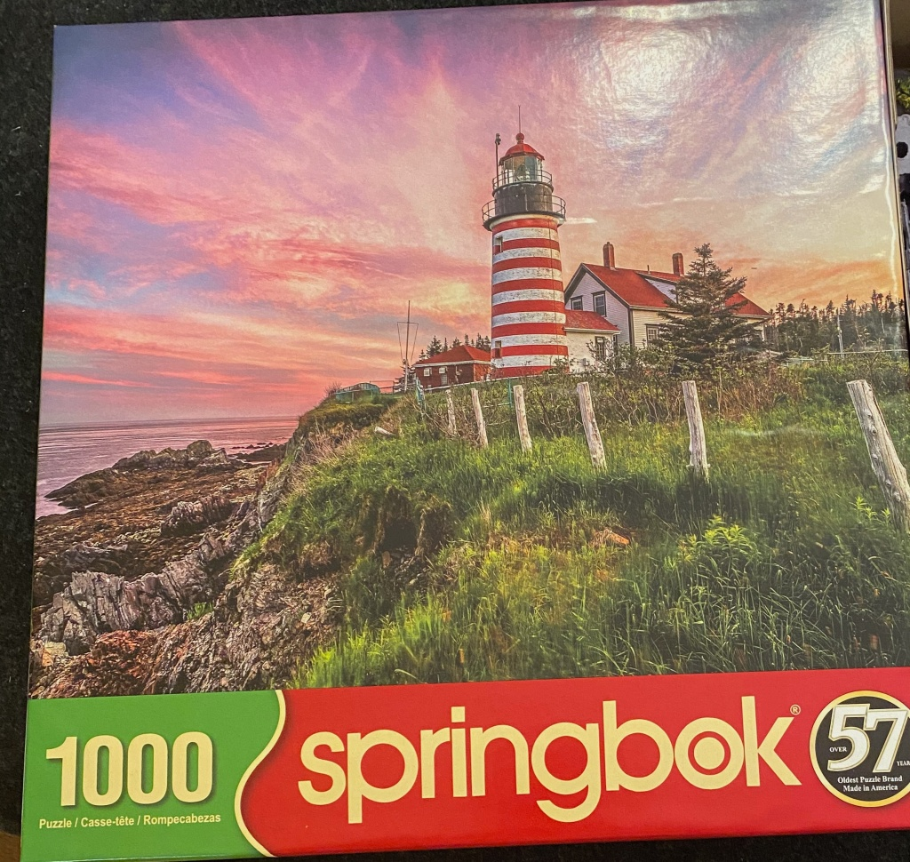 A box for a 1,000-piece Springbok puzzle, showing a picture of a red-and-white striped lighthouse on a grassy bluff, in front of a pink and peach colored sunset sky.
