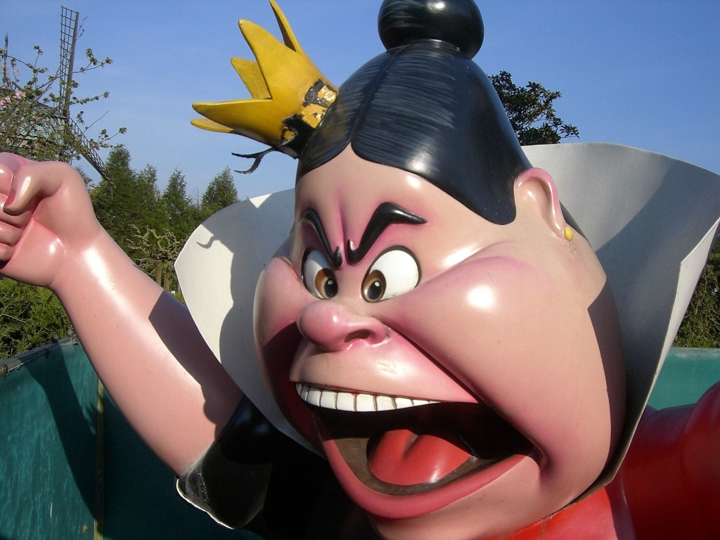 A statue of the Queen of Hearts from Disney's Alice in Wonderland, in closeup showing her clenched fist and screaming, angry face.