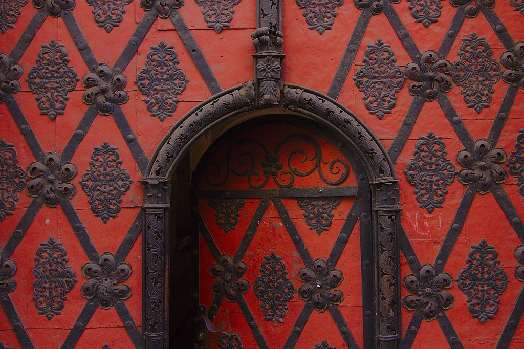Close-up image of the top half of a door patterned exactly like the wall it is set into. The door is ajar.