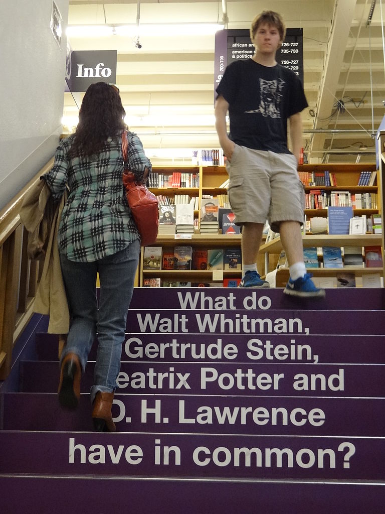"A set of purple stairs inside of Powell's bookstore in Portland, Oregon. Printed on the stair risers is this question: ""What do Walt Whitman, Gertrude Stein, Beatrix Potter and D.H. Lawrence have in common?"""