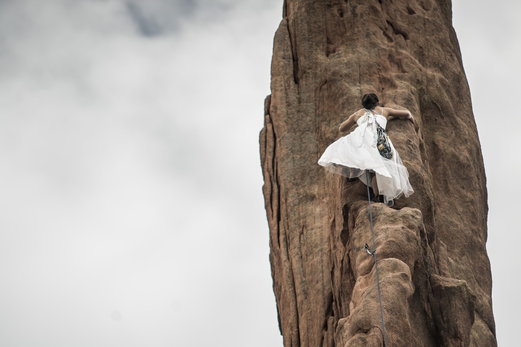 Looking up at a dark-haired woman wearing a white dress as she climbs a tall rock face.