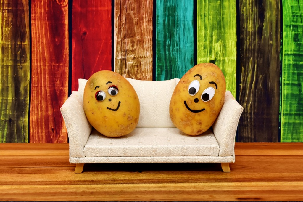 Two potatoes with cartoon faces drawn on them, sitting side by side on  a dollhouse-sized couch.